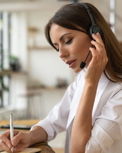 focused-woman-consultant-in-shirt-wear-headphones-communicating-with-clients-talking-on-video_t20_rL09dl